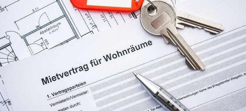 Wohnungsschlüssel für eine Mietwohnung auf einem Mietvertrag