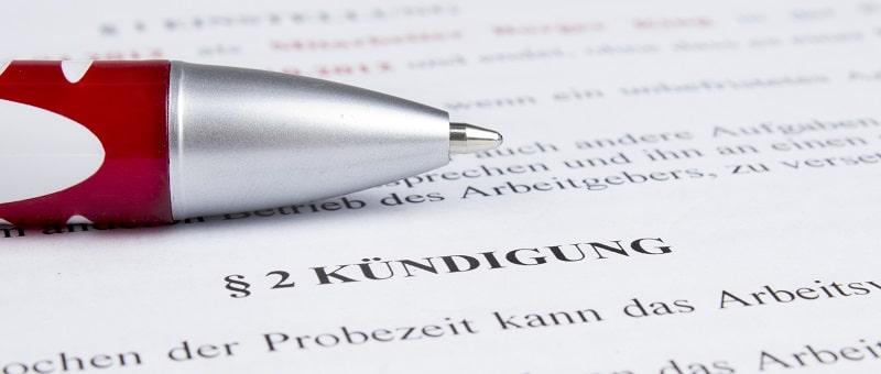Kugelschreiber auf einem Paragraph zum Thema Kündigung laut Arbeitsrecht